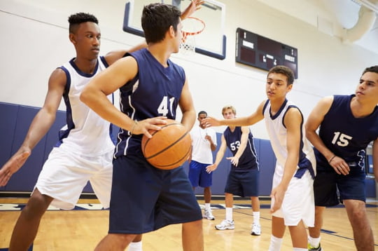 a group of teens play basketball in a gym